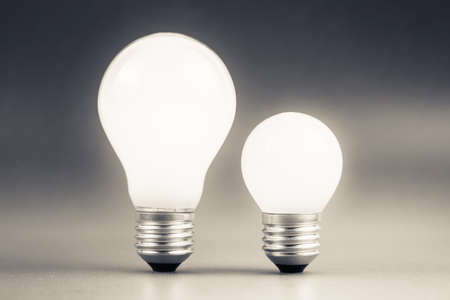 comparative: Comparative big and small light bulb, small and medium sized business, coaching, training, or other comparison concept