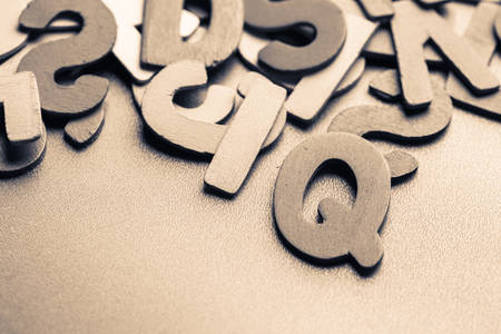 iq: Closeup the letters I and Q of scattered wood letters for the concept about IQ (Intelligence quotient ) Stock Photo