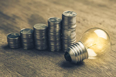 Small light bub glowing and heap coins stair, start financial planning
