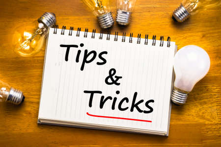Tips and Tricks text on notebook with glowing light bulbs Archivio Fotografico