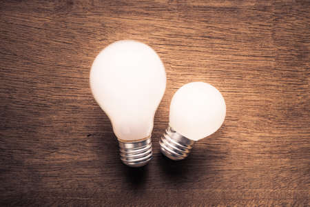 medium size: Small and big light bulb, small and medium sized business, coaching, training, or other comparison concept