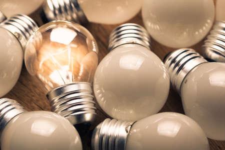 focos de luz: Transparente bombilla que brilla intensamente entre las bombillas de luz blanca Foto de archivo