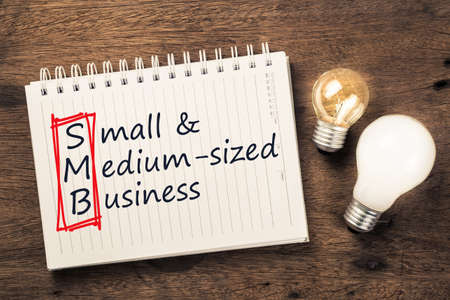 SMB or Small and Medium Sized Business text on notebook with two different light bulbs Imagens