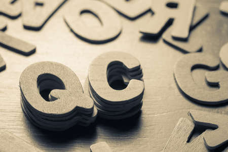 qc: Stack of Q and C alphabet in scattered wood letters, QC or Quality Control concept Stock Photo