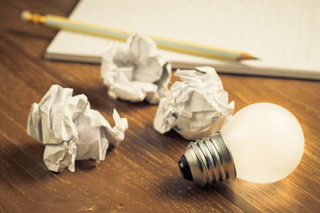 Idea for writing, glowing light bulb and crumbled paper balls