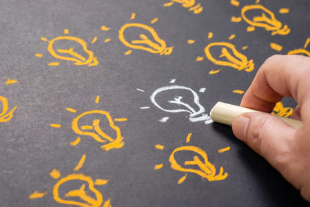 Similar but different, hand drawing white light bulb among the orange ones Stock Photo