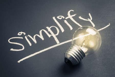 Hand writing Simplify topic on chalkboard with glowing light bulb Фото со стока - 74240577