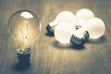 Individual light bulb glowing out of the group Standard-Bild