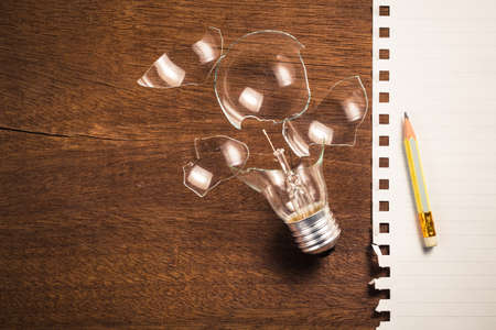 stumped: Broken light bulb and paper for writing concept Stock Photo
