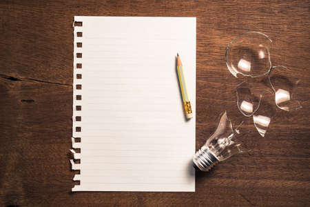stumped: Paper and pencil with broken light bulb for writing concept