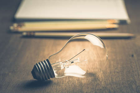 Light bulb with pencils and notebook on background Foto de archivo