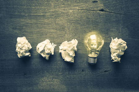 differentiation: Light bulb glowing in a row of crumpled ball paper