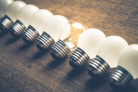 differentiation: Different light bulb glowing in the row Stock Photo