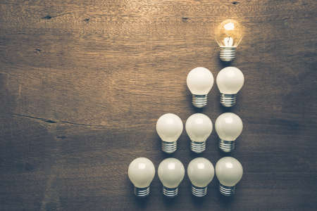 differentiation: Different light bulb glowing on the top of the level Stock Photo