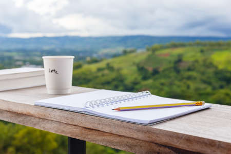 Opened notebook with pencil and cup of coffee, prepare to write at the balcony by the mountain view environment