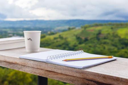 Geopende notitieblok met potlood en kopje koffie, voorbereiden om te schrijven op het balkon door de omgeving met uitzicht op de bergen Stockfoto - 84488535