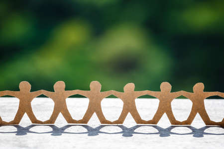 Human chain paper setup at outdoor in sunlight with blurred green forest on background Standard-Bild