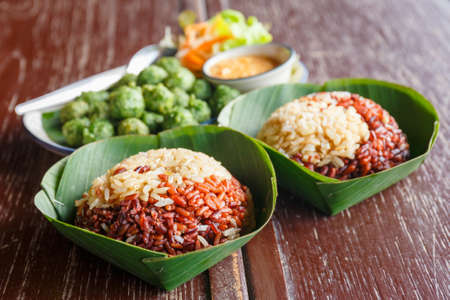 Organic steamed brown rice in banana leaves dish, traditional Thai meal