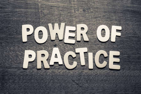 Power of Practice by wood letters on wood background