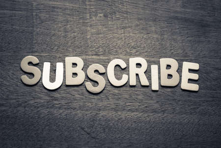 Subscribe  by wood letters on wood background