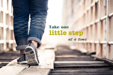 Take One Little Step At a Time - inspiration quote on concept photo, woman walking on the wood bridge