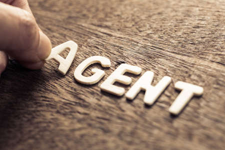 Hand arrange wood letters as Agent word for marketing concept