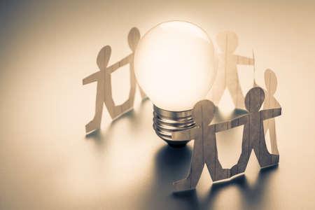 Human chain paper with glowing light bulb Standard-Bild