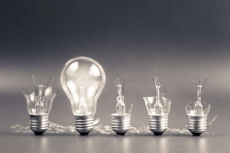 Perfect light bulb glowing in a row of broken bulb for solution concept