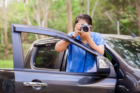 Woman take a photo from the opened car door of pick-up truck with green forest on background, driving travel for photography