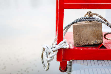 Square stone anchor and old rope on the pontoon