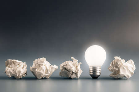 Small light bulb glowing in a row of crumpled paper balls, inspiration, problem and solution concept