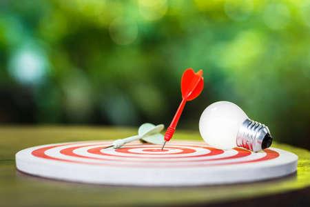 Freccette rosse colpite sul bersaglio con lampadina bianca sul tavolo, definizione intelligente degli obiettivi Archivio Fotografico