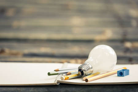 Light bulb and writing equipments on the bamboo table 스톡 콘텐츠