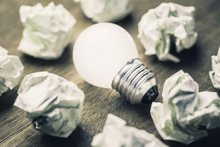Glowing light bulb among the crumpled paper balls 스톡 콘텐츠