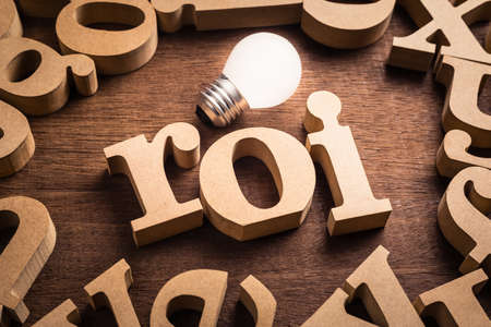 ROI abbreviation (Return on Investment) in scattered wood letters with glowing white light bulb Stockfoto