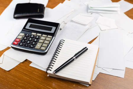 Notebook and pen on many receipts on the table with calculator and wallet