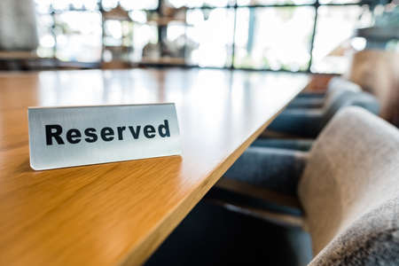 Reserved metal sign on clear wood table, big table in the cafe for diner, work or meeting event