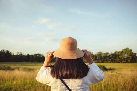 Back of single woman wearing the hat on her head ready to wander in the field