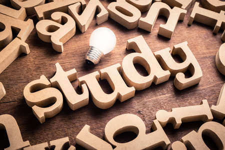STUDY word by wood alphabet scattered on the table with glowing light bulb
