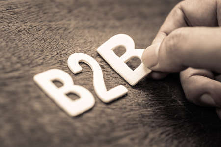 Hand place a wood letters as B2B abbreviation (Business to Business)