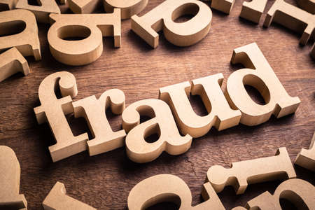 FRAUD word by wood alphabet scattered on the table