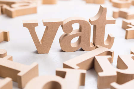 VAT (Value-Added Tax) word by wood alphabet scattered on the table Archivio Fotografico