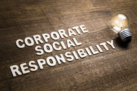 Corporate Social Responsibility or CSR, text with glowing light bulb as creativity and success idea