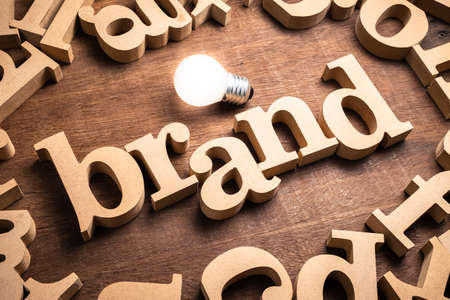 BRAND word in scattered wood letters on the table with glowing light bulb Stockfoto