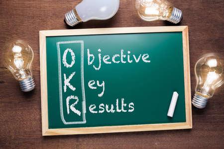 OKR oder Objective Key Results Akronymtext auf Tafel mit vielen leuchtenden Glühbirnen