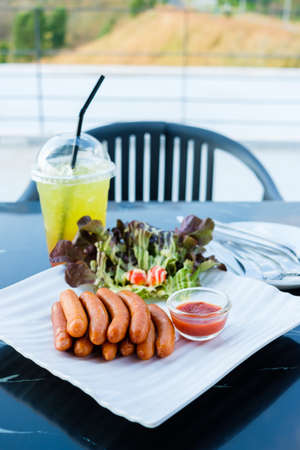 Pile of sausages on the white plate served with ketchup, salad and iced juice, afternoon appetizer at the outdoor table of the restaurant