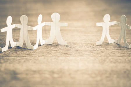 Two paper human chains disconnect caused by loosing doll in a role between them, lost friendship, teamwork or connection concept