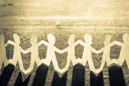 Paper human chain against the light on wood background Stock Photo