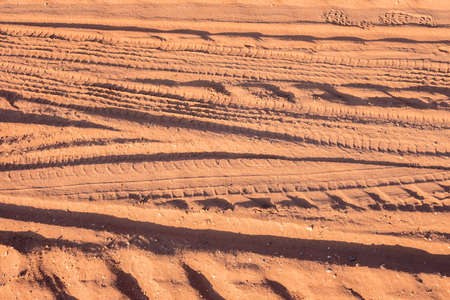 Many kinds of vehicle wheel tracks (car, tractor, motorcycle and bicycle) on dirt road, pattern of tyre tracks, abstract transportation background and sand texture