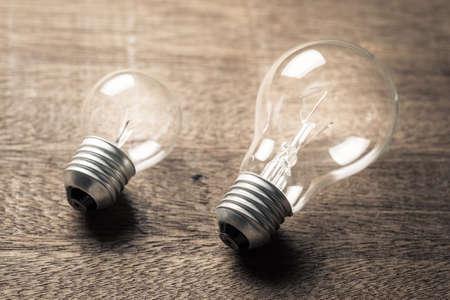 Big and small light bulbs glowing on wood table
